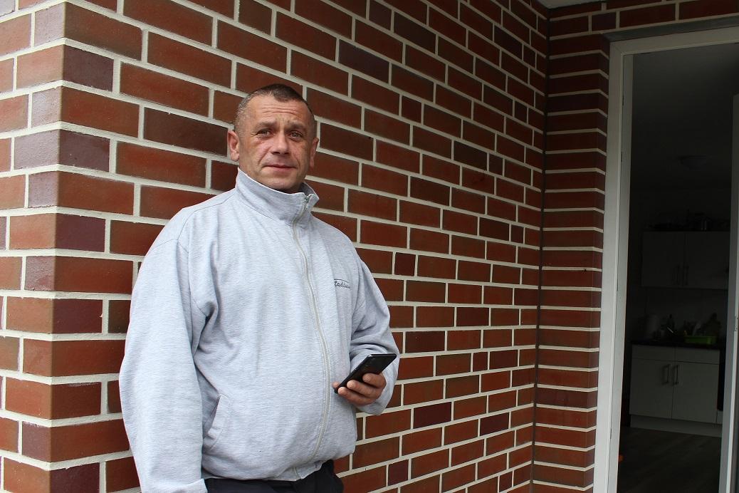Ein Toennies-Arbeiter steht vor seiner Unterkunft und raucht.